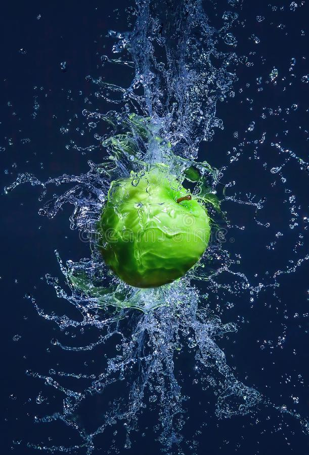 Latający zielony jabłko w wodnych pluśnięciach obrazy royalty free