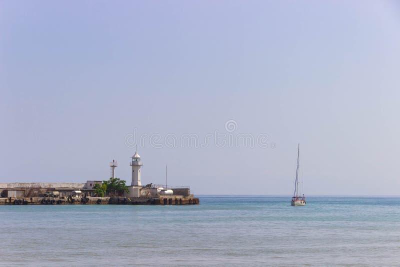 Latarni morskiej i żagla łódź przy lato błyszczącym dniem zdjęcie stock