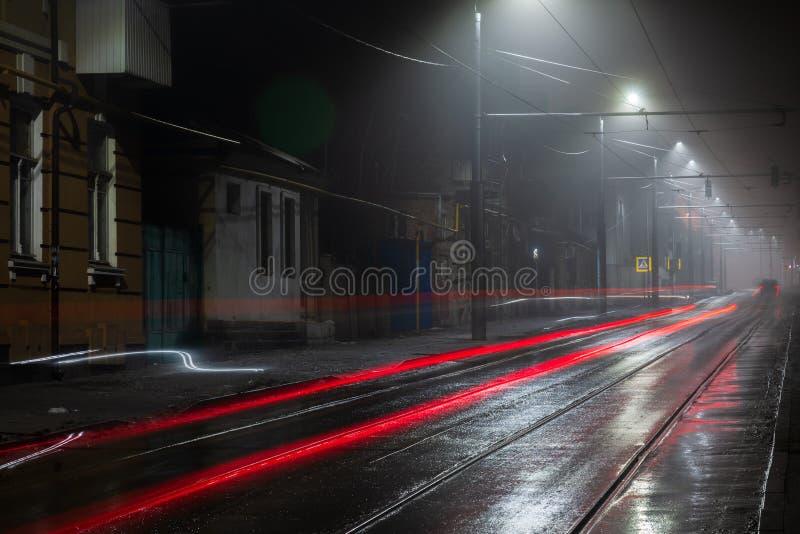 Latarni ulicznej mg?owa mglista noc Tramwajowa trasa na miasto ulicie zdjęcia royalty free