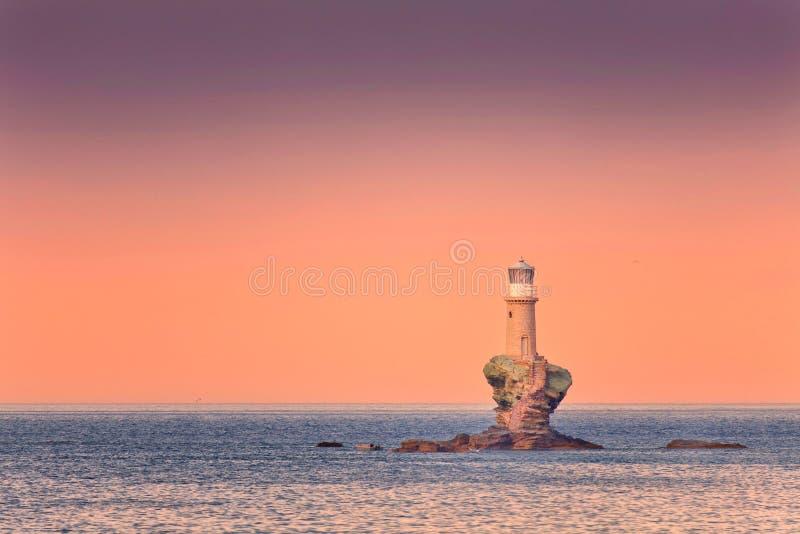 Latarnia morska na skale przy zmierzchem zdjęcia royalty free