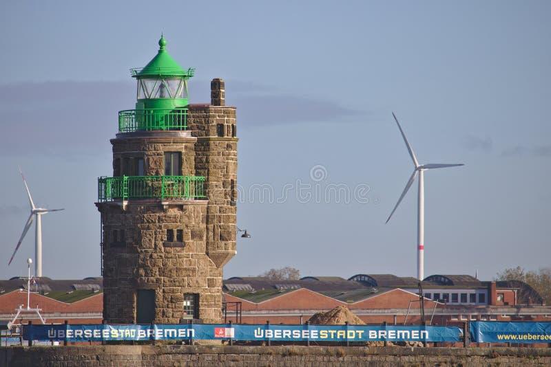 Latarnia morska przy schronienia wejściem z przemysłowymi składowymi budynkami i sił wiatru stacjami Bremen, Niemcy, Listopad - 6 obrazy royalty free