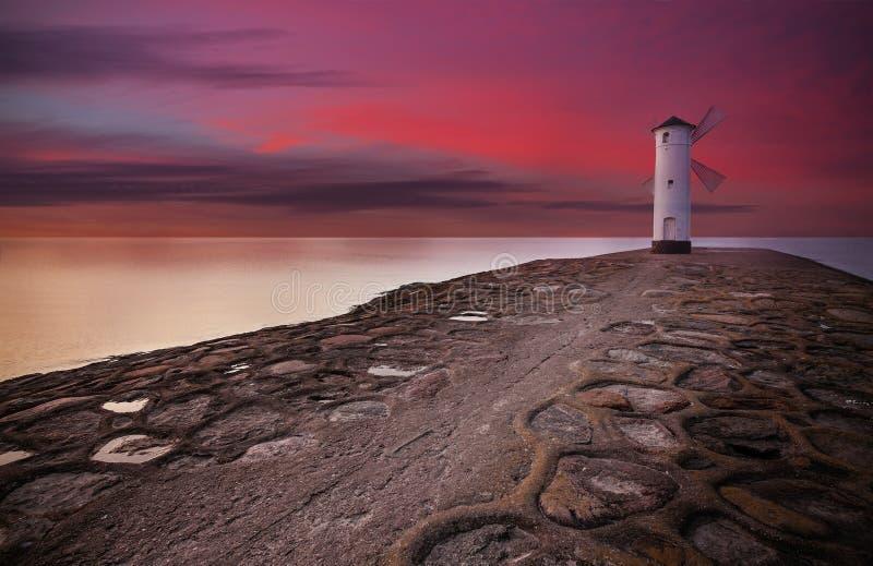 Latarnia morska wiatraczek z dramatycznym zmierzchu niebem zdjęcia royalty free