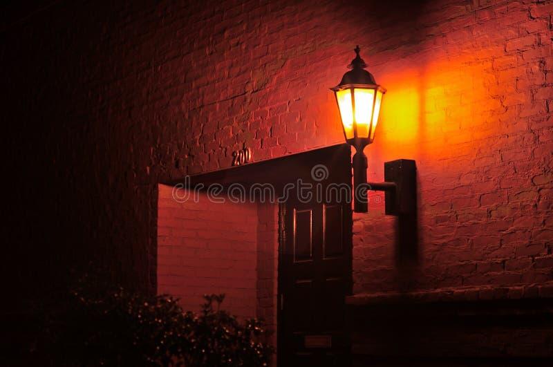 Latarnia uliczna na czerwonym ściana z cegieł rozjaśnia drzwi w nocy obraz stock