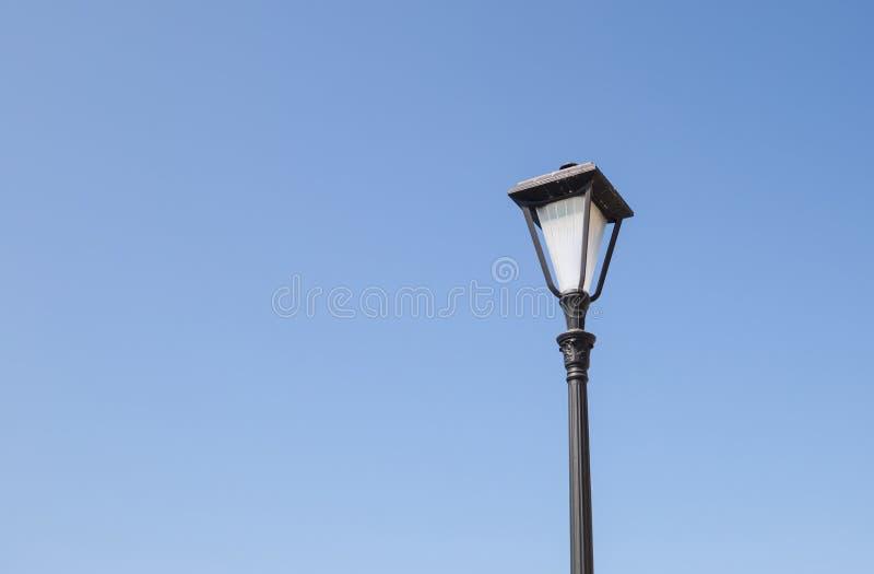 Latarnia uliczna w czerni z jeden lampą w antyka stylu na niebieskim niebie obrazy royalty free
