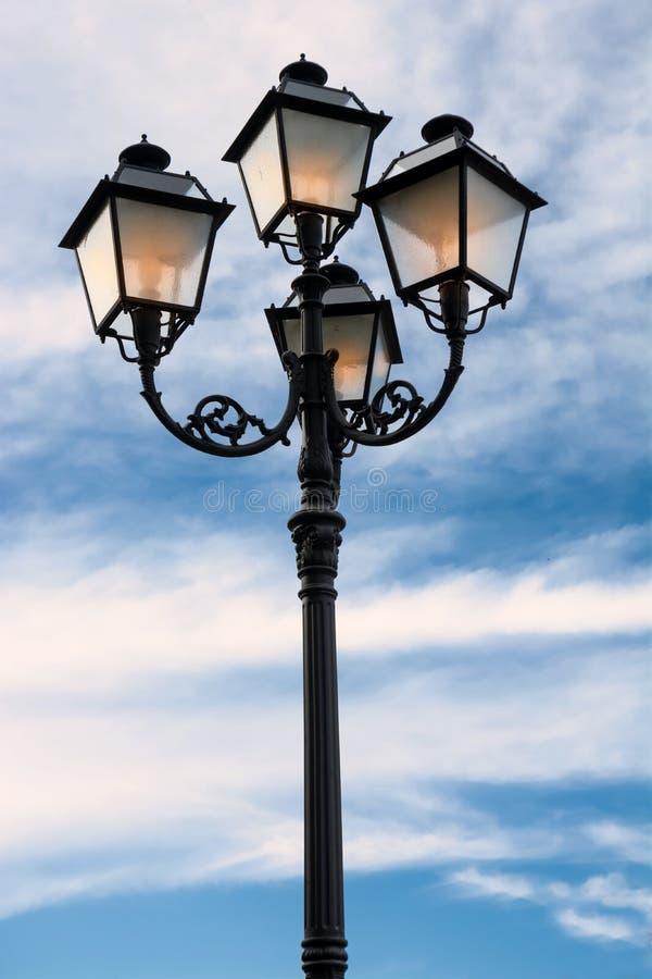 Latarnia uliczna zaświecająca przy półmrokiem zdjęcia royalty free