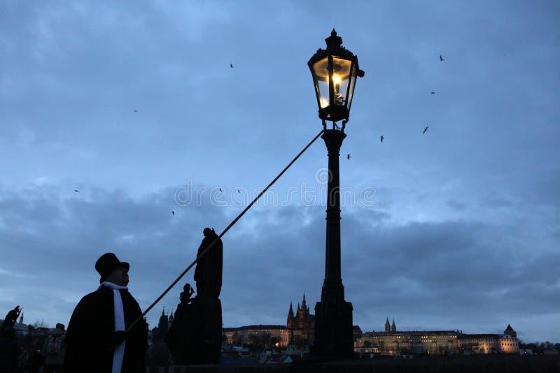 Latarnik zaświeca ulicznego benzynowego światło przy Charles mostem w P fotografia royalty free