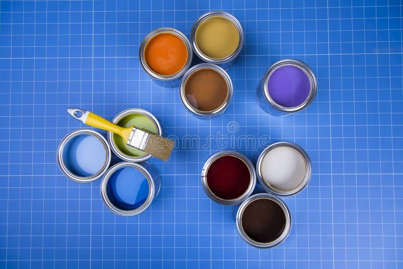 Latas abertas da pintura, escova, fundo azul imagens de stock
