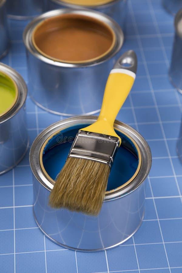 Latas abiertas de pintura, cepillo, fondo azul imagen de archivo