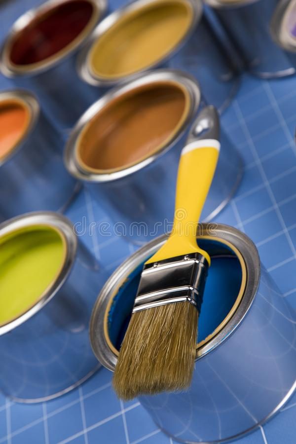 Latas abiertas de pintura, cepillo, fondo azul foto de archivo libre de regalías