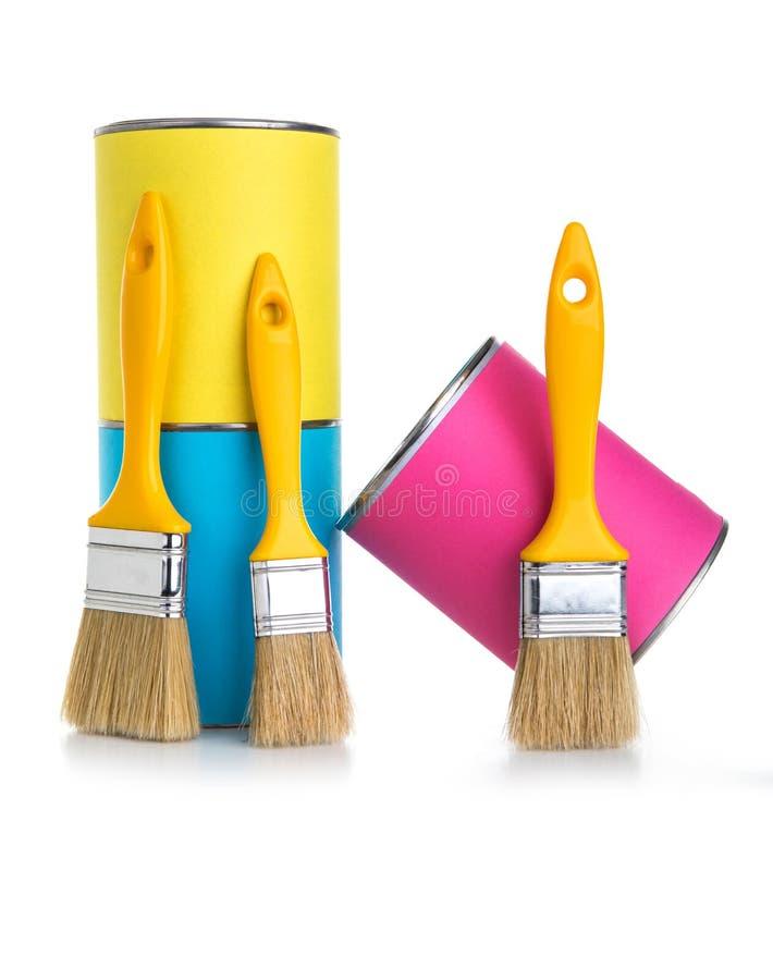 Latas amarillas, azules y rosadas de pintura y de brocha aisladas encendido imagen de archivo