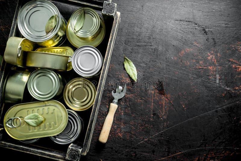 Latas cerradas de comida enlatada en una caja con un abrelatas fotografía de archivo