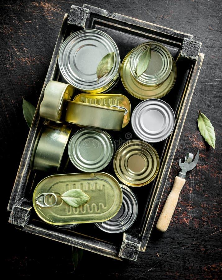 Latas cerradas de comida enlatada en una caja con un abrelatas fotos de archivo libres de regalías