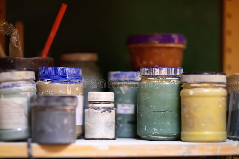 Latas coloridas da pintura na prateleira na oficina fotos de stock royalty free