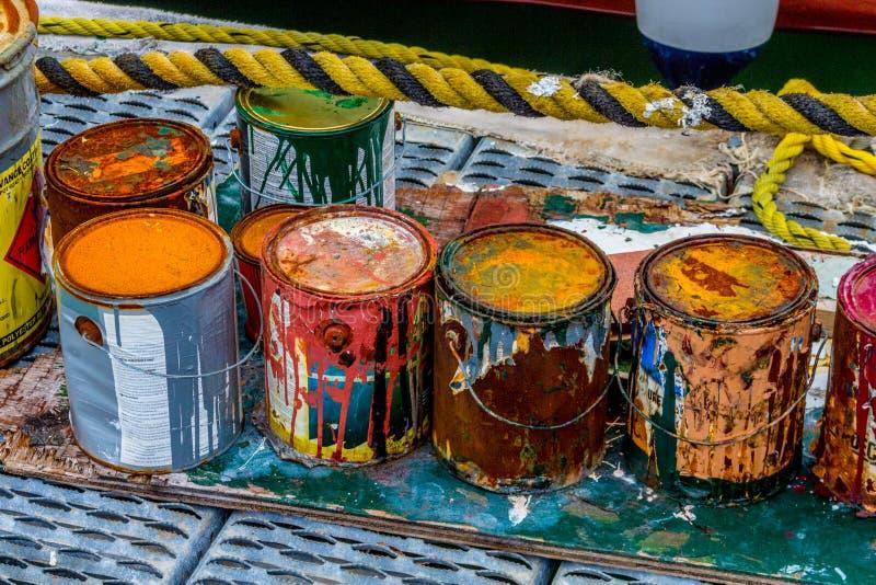 Latas coloridas de la pintura que aherrumbran foto de archivo