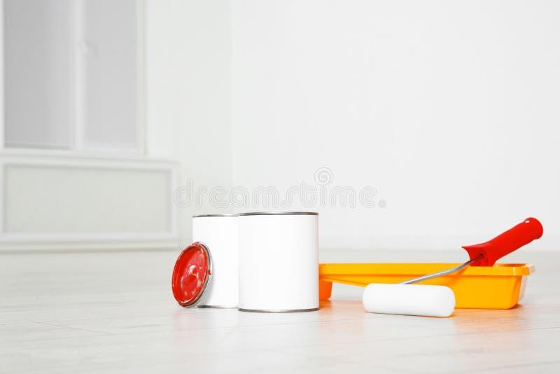Latas de herramientas de la pintura y del decorador en piso de madera foto de archivo libre de regalías