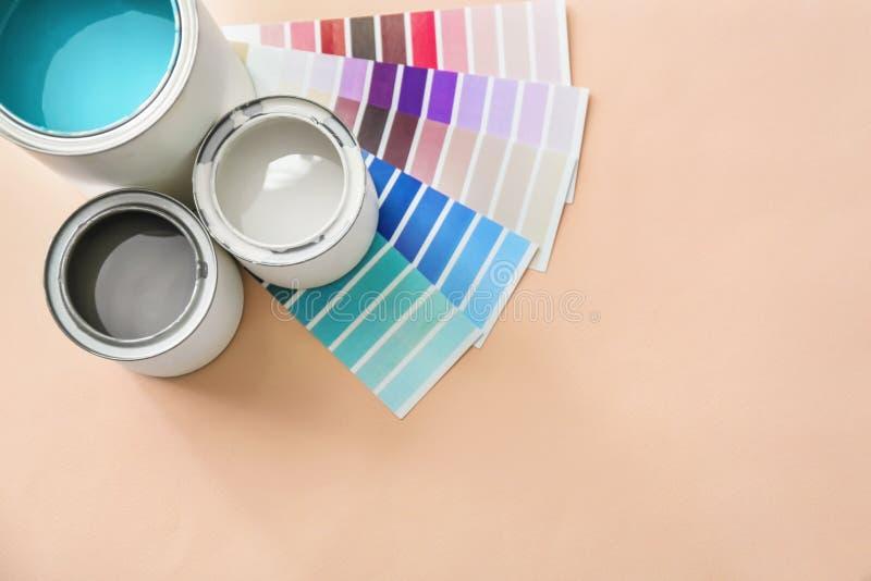 Latas de la pintura con las muestras de la paleta de colores en fondo ligero foto de archivo