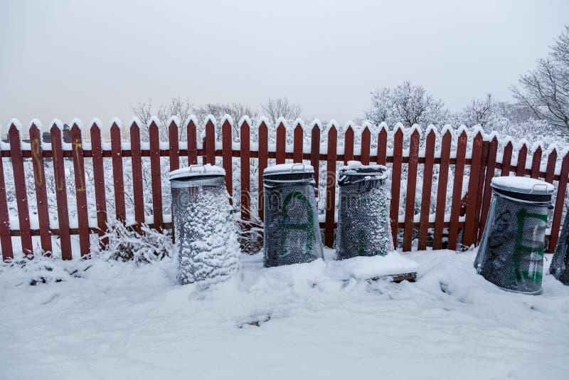 Latas de lixo em um parque nevado em um inverno a Dinamarca foto de stock