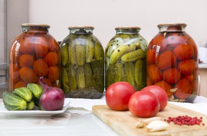 Latas de pepinos y de tomates conservados en vinagre conservados en vinagre, verduras frescas fotos de archivo