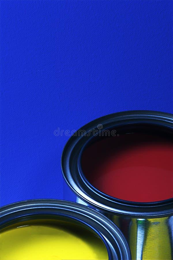 Latas de pintura, colores primarios, rojo y amarillo, adornando imagenes de archivo