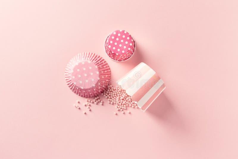 Latas del mollete del vintage y perlas del azúcar en fondo del rosa en colores pastel fotos de archivo