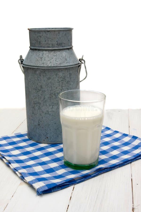 Latas e vidro do leite em um guardanapo checkered fotografia de stock