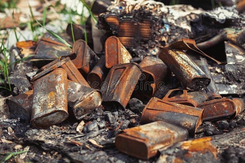 Latas oxidadas viejas quemadas lanzadas lejos en el bosque fotografía de archivo
