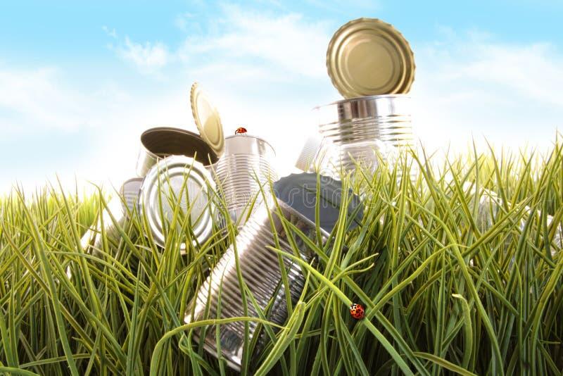 Latas y botellas vacías olvidadas en hierba fotografía de archivo libre de regalías