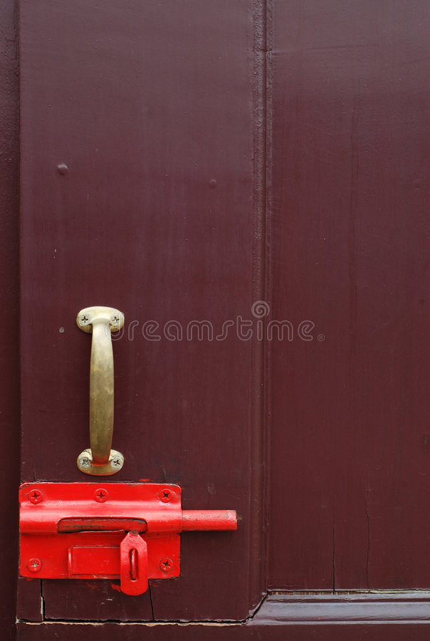 Latch lock. Old red latch lock on wooden door royalty free stock photo