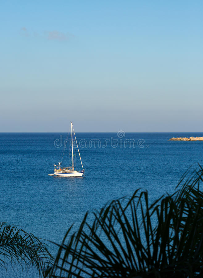 In the late afternoon a sailing boat, sails to a harbor. stock image