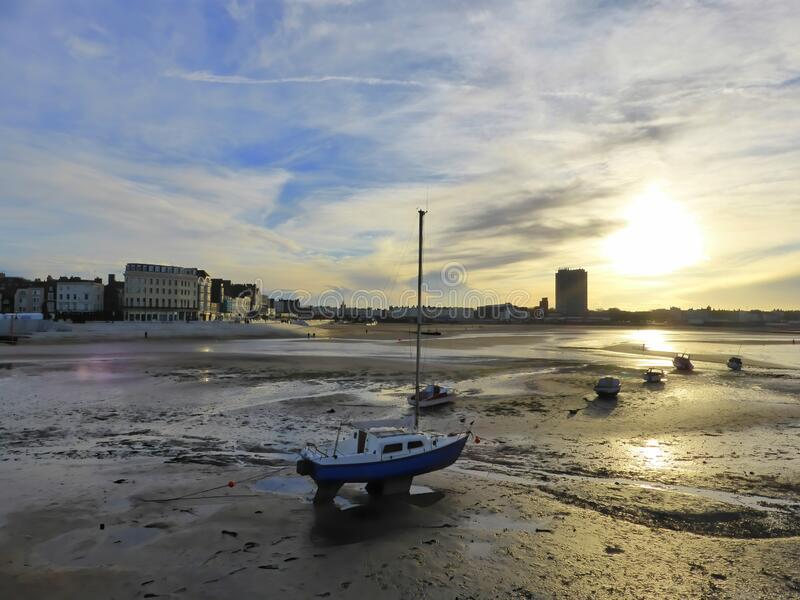 Late afternoon sun on beach resort. Late afternoon sun and small boats on the beach at Margate in Kent, England royalty free stock images