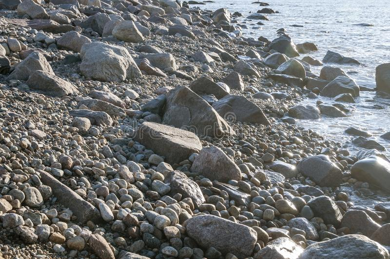 Rocky coastline on Gooseberry Neck. Late afternoon sun low on water softens rocky Buzzards Bay shoreline stock photo