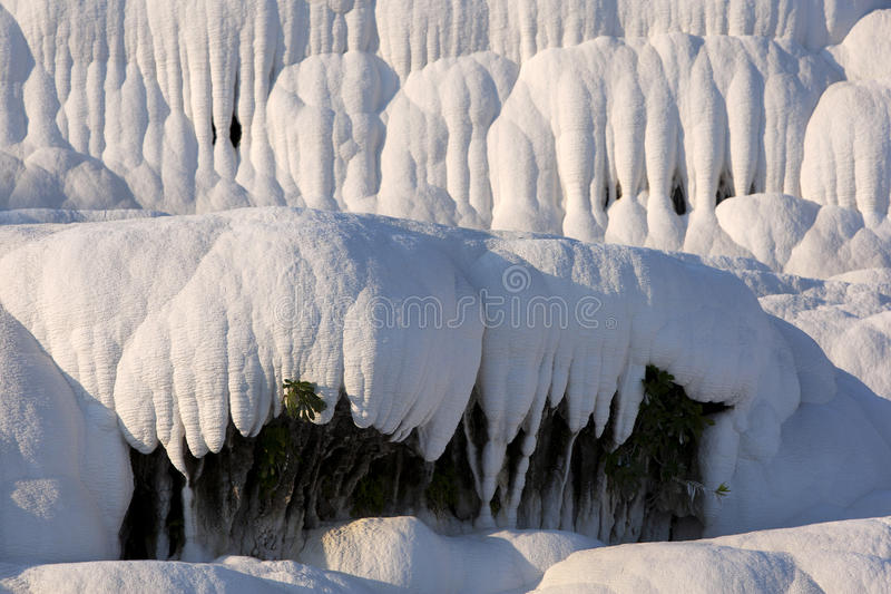 The late afternoon sun shines on a spectacular landscape at Cotton Castle (travertines) at Pamukkale in Turkey. The landscape was formed over thousands of royalty free stock photo