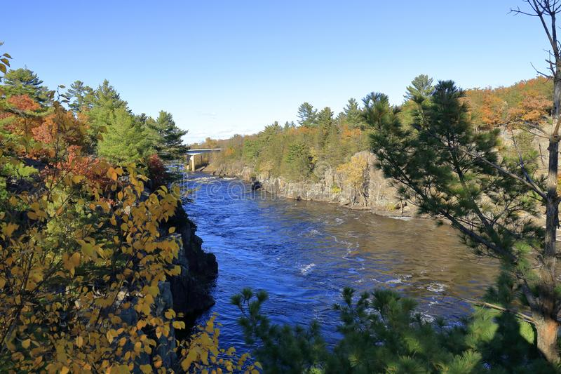 Late fall picture of River. Late fall river and river bluff picture with rapids and many trees stock image