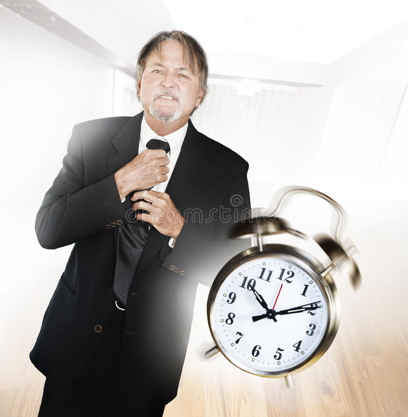 Late man with alarm clock. A frustrated man adjusts his tie as the alarm clock rings