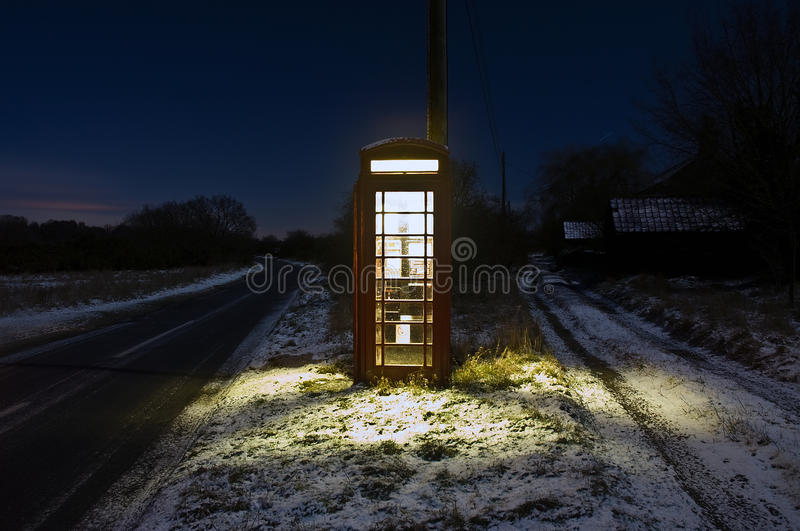 Late night call Center. This is a long exposure photo of a British telephone box taken at night time during winter and snow covered ground. The location is in royalty free stock photo