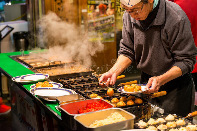 Late Night Dining. A Japanese man grills takoyaki at a food stall on December 27, 2014 in Osaka, Japan royalty free stock photography
