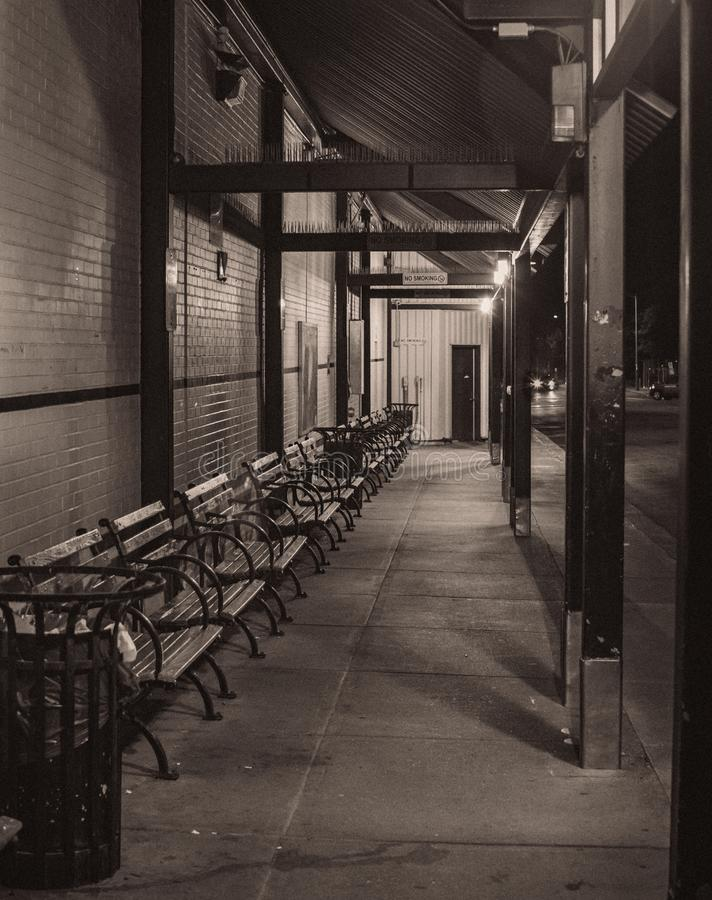 Late night empty benches at a bus stop in black and white. stock images