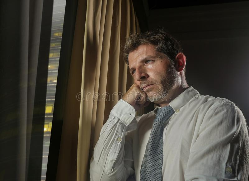 Late night office portrait of young stressed and overwhelmed businessman working under pressure feeling depressed and worried royalty free stock image