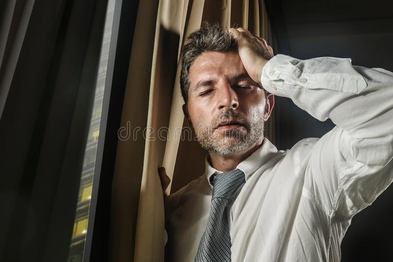 Late night office portrait of young stressed and overwhelmed businessman working under pressure feeling depressed and worried. Suffering anxiety crisis leaning stock image