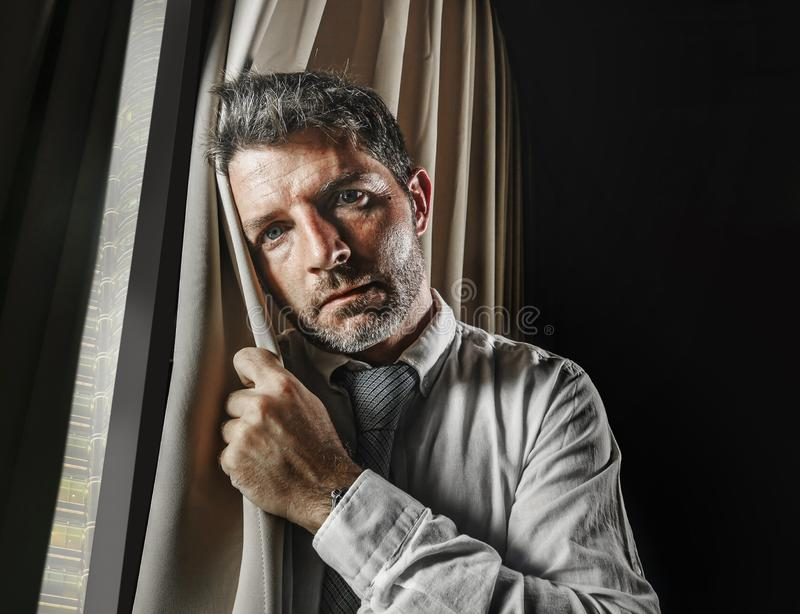Late night office portrait of young stressed and overwhelmed businessman working under pressure feeling depressed and worried. Suffering anxiety crisis leaning stock photo