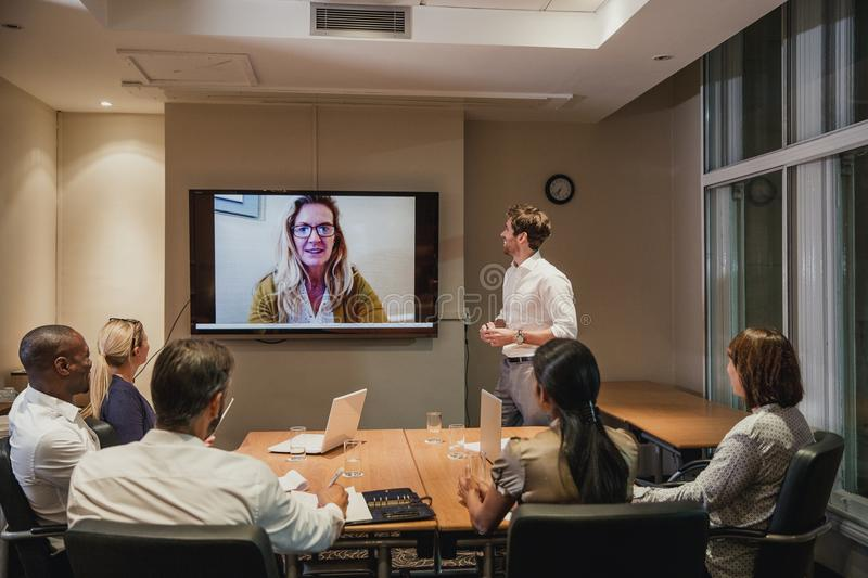 Late Night Video Conference Meeting. Group of business people having a late night video conference meeting. Sitting around a conference table talking and royalty free stock photos