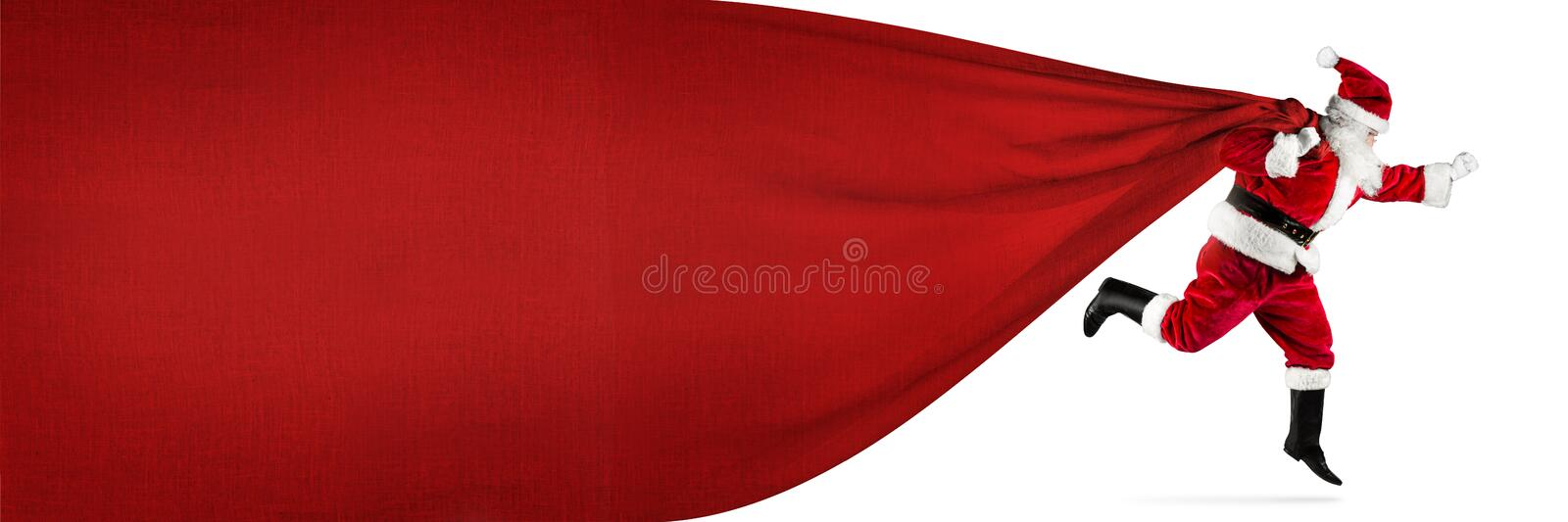 Late Santa claus in a hurry with traditional red white costume a. Nd big gift bag with copy space running jumping abstract funny christmas xmas background royalty free stock images