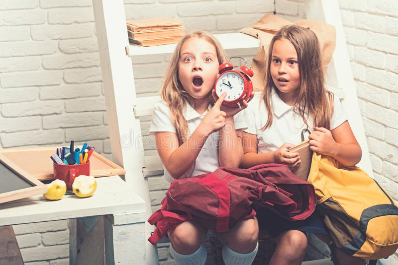 Late. Shoked small girls show time on clock. small kids late to school. royalty free stock photography
