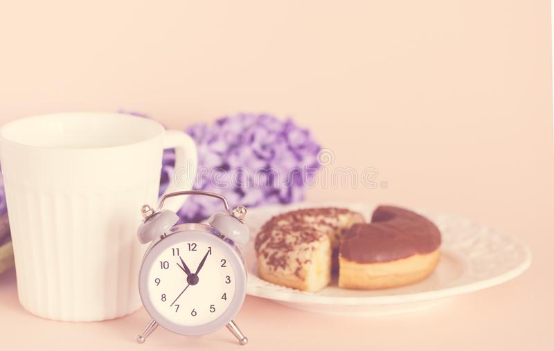 Late spring breakfast with coffee, delicious chocolate muffins, flowers - purple hyacinths and retro alarm clock stock photos