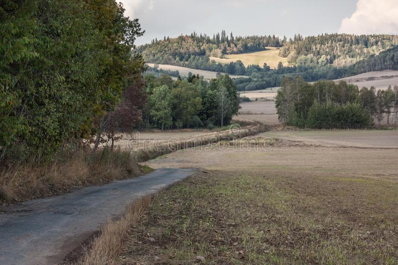 Late summer landscape in the picturesque Kaczawskie Mountains. Cultivated fields after the harvest. Deep dark green trees, earth in shades of brown, straw stock photography