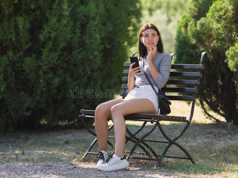 Late-teens girl at the park. Eighteen-year-old girl sitting on a bench in the park and talking on a smartphone royalty free stock photos