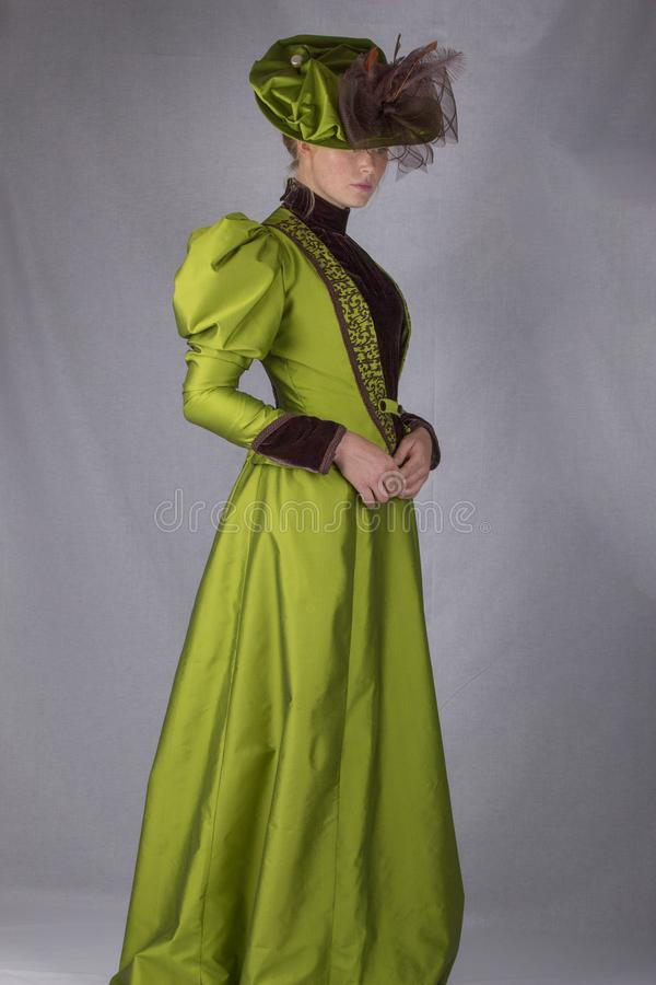 Late Victorian woman in green silk ensemble stock image