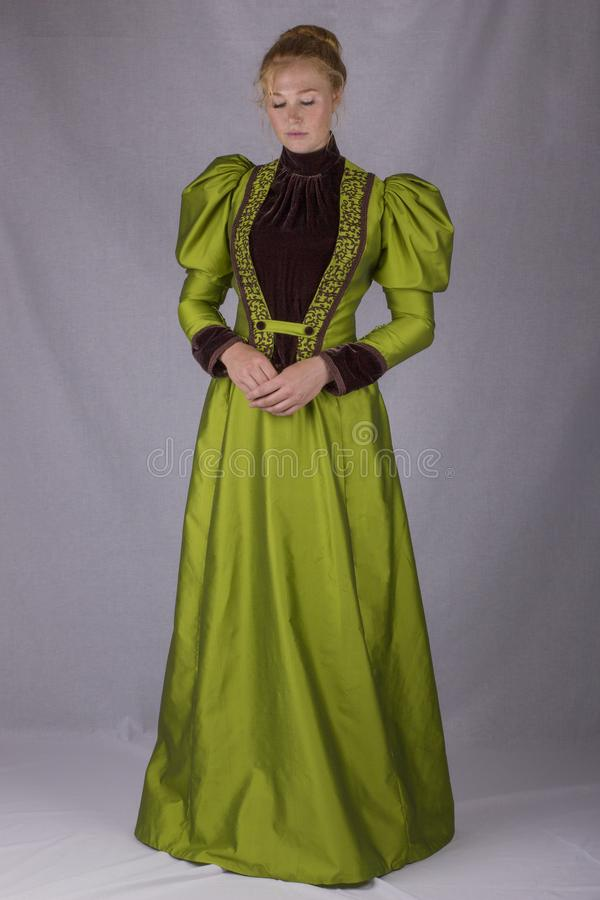 Late Victorian woman in green silk ensemble. A late Victorian 1890`s woman wearing a green silk jacket, hat and skirt with a brown velvet blouse against a white royalty free stock image