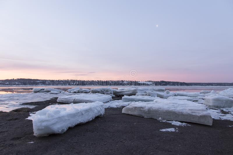 Late winter blue hour sunrise view of large ice chunks on the rocky banks of the St. Lawrence river. In the Cap-Rouge area of Quebec City, Quebec, Canada stock photography