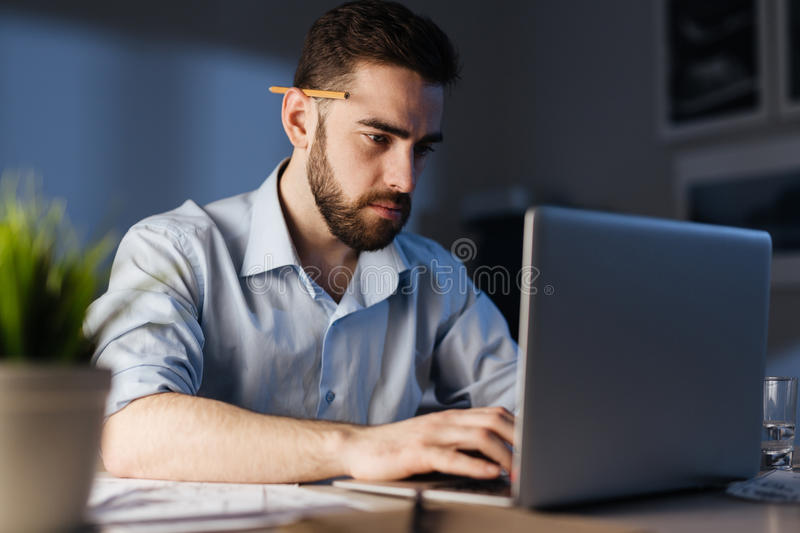Late work. Businessman typing plan for next day late in office stock photo